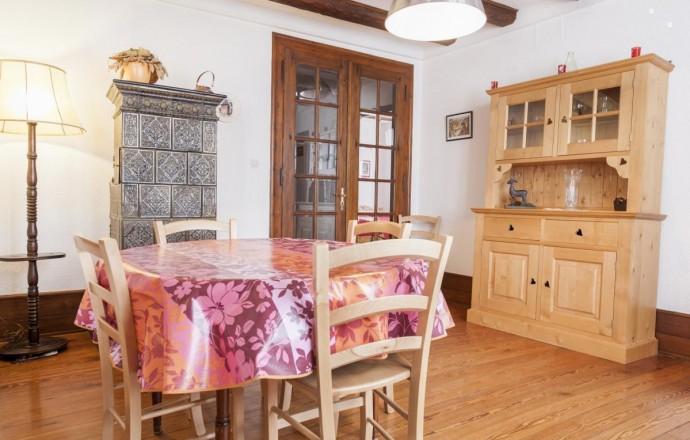 Salle à manger spacieuse avec poutres apparentes et décorée de gravures de Hansi