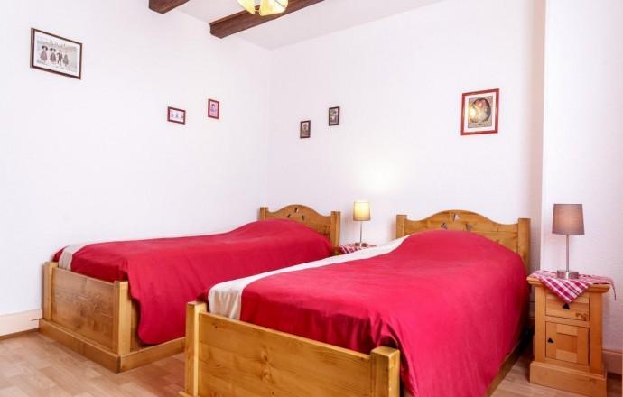 Chambre n°2 du gîte : 2 lits 1 personne, meubles en chêne et poutres apparentes