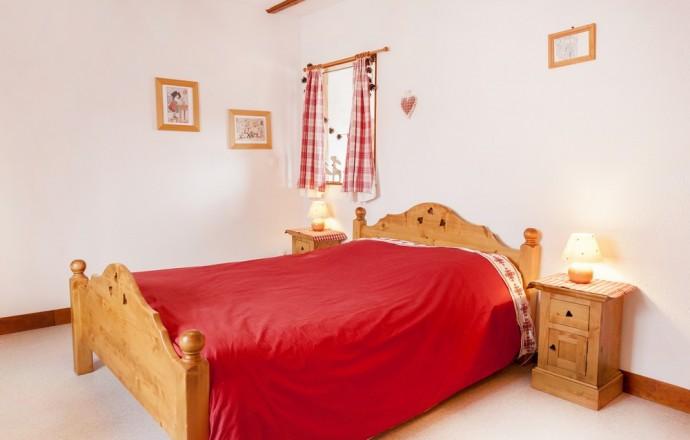 Chambre avec lit 140x190,  poutres apparentes, meuble en sapin,  couette douillette et gravures Hansi