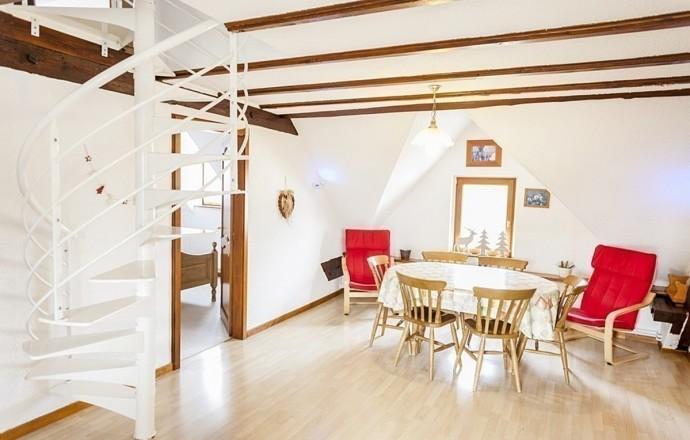 Salle à manger agréable et rustique avec poutres et charpente apparentes